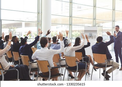 Rear view of group of diverse business people raising hands while listening to handsome mixed-race businessman at conference