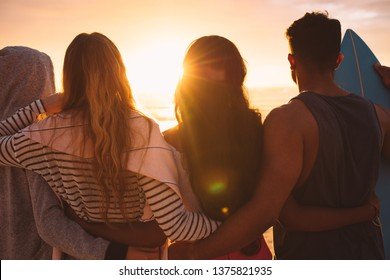 Rear view of a group of friends standing together on beach holding each other. Man standing with his women friends at the beach looking at the sunset holding a surfboard.