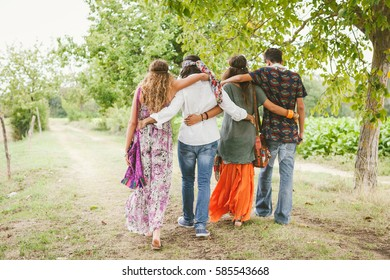 Rear view of Group of Hippie People Walking Away in Nature