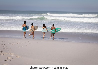 Rear view of group of multi-ethnic friends running to the waterside with surfboards  while having fun at beach in the sunshine