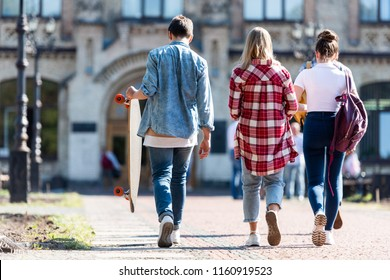 rear view of group of teen students walking in front of old college building