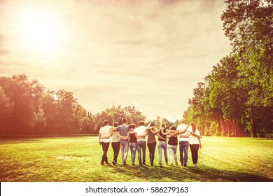 Rear view of group of Teenage Friends walking in the Park at Sunset