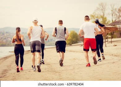 Rear view of a group young friends running together on the beach.