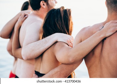 Rear view of group of young multiethnic friends women and men at the beach in summertime hugging - teamwork, friendship, together concept