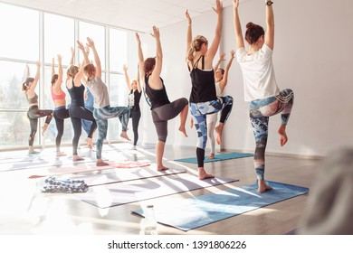 Rear view group of young unidentified women doing vrikshasana during yoga classes in a bright gym with large windows. Flatfoot disease prevention and poor posture concept