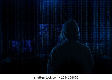 Rear View Of A Hacker Using Multiple Computers For Stealing Data On Desk