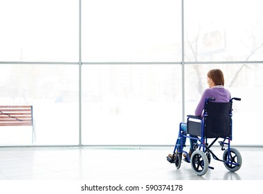 Rear view of handicapped young woman sitting in wheelchair, looking at window and daydreaming