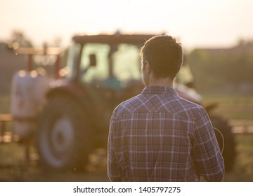 Rear view of handsome farmer standing in front of tractor with sprayer in field