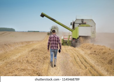 Rear view of handsome farmer with tablet walking in front of combine harvester during harvest in field