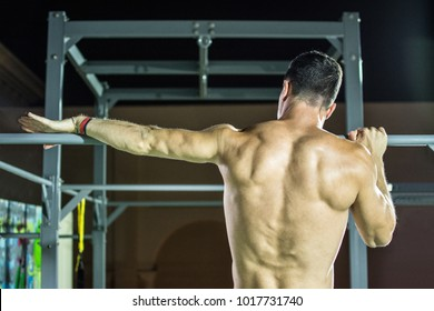 Rear view of handsome man back. Calisthenic workout on horizontal bar in the outdoor gym at night.