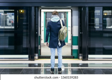 Rear view of handsome man in blue coat and green backpack behind stands in front of the open doors of the subway and waiting for next train. Underground platform. Way to work. Urban life concept.