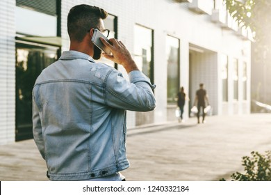 Rear view. Handsome smiling hipster businessman with beard, in denim jacket, trendy glasses walks around city, calls on mobile phone. Happy guy standing outdoor and talking on cell phone. Lifestyle.