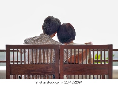 Rear view of a happy asian middle aged a couple on bench
