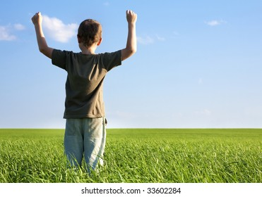 Rear view of happy boy raising his arms while standing in bright green grass under blue sky