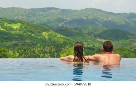 Rear view of happy couple in the pool looking at mountain landscape. Enjoying beautiful mountains. Man, woman together on summer travel to luxury resort. Summertime relax.