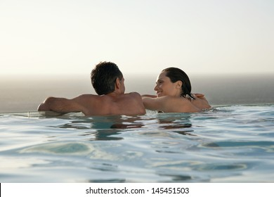 Rear view of happy couple relaxing in infinity pool at resort