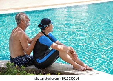 rear view happy elderly caucasian husband and elderly asian wife take a break while swimming outdoor in pool during retirement holiday with relaxation and smiling