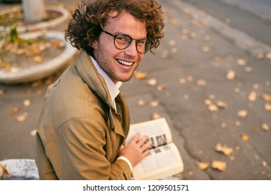 Rear view of happy handsome young man reading book outdoors. College male student carrying books in campus in autumn street. Smiling smart guy wears spectacles and curly hair reading books in street