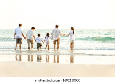 Rear view of Happy Multi Generation Asian family relaxing and having fun together on the beach in summertime. Big family parents with child boy and girl enjoy summer lifestyle travel holiday vacation.