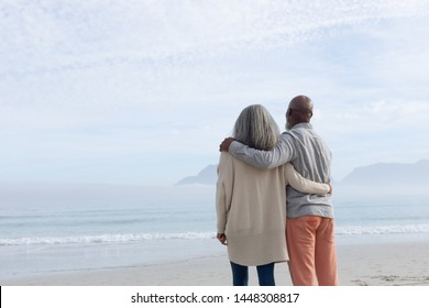 Rear view of happy senior African-American couple standing next to each other while looking at the sea and mountains on beach on beautiful cloudy day. Authentic Senior Retired Life Concept