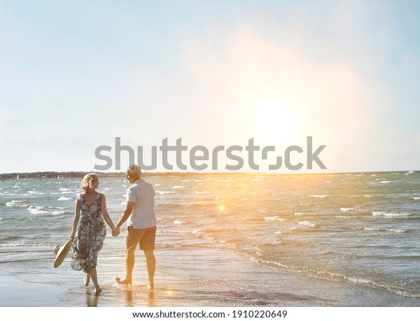 Rear view of happy senior couple holding hands and walking on tropical beach