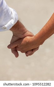 Rear view of happy senior man and woman couple holding hands on a beach.