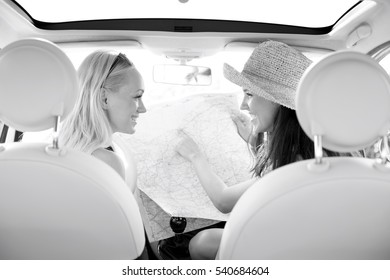 Rear view of happy women reading map in car