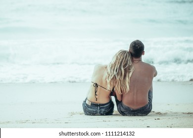 Rear view of happy young Caucasian couple sitting together on seashore