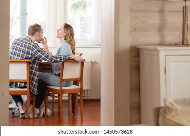 Rear view of a happy young couple having lunch in the living room of their cozy little country house with their beloved faithful dog