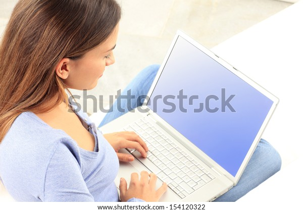 Rear view of happy young woman working on laptop at home