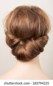 Rear view of the head of a young redhead woman with a bun