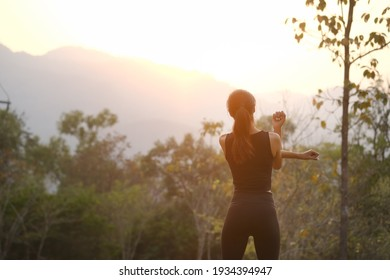 Rear view healthy young woman stretching in the park before running at the sunset. - Shutterstock ID 1934394947