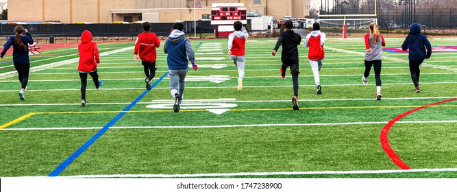 Rear view of high school track team of boys and girls performing warm up running drils side by side on a greeen turf field.