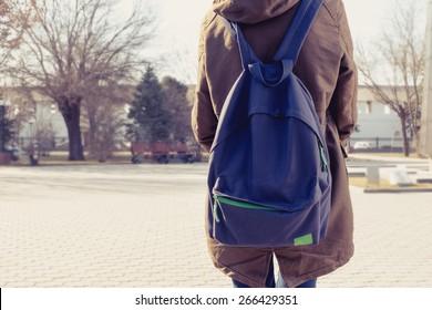 Vista traseira da menina hipster carring mochila em suas costas, copyspace.
