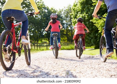 Rear View Of Hispanic Family On Cycle Ride In Countryside