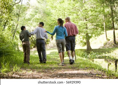 Rear view of Hispanic family walking along trail in park, boys 10 and 14 years old