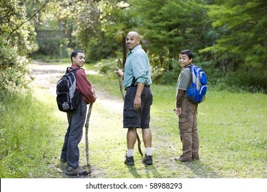 Rear view of Hispanic father and two sons (10 and 14 years) hiking on path in woods
