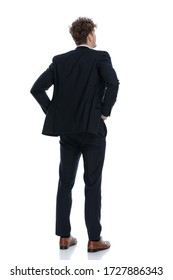 Rear view hopeful businessman holding his hands on his waist while wearing suit and standing on white studio background