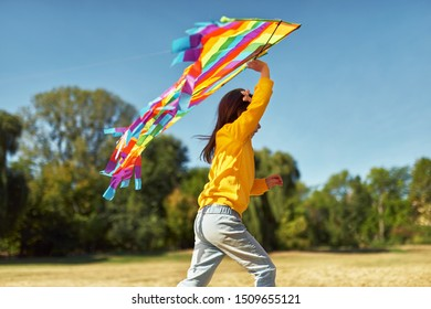Rear view image of happy child little girl running with a big colorful kite on a sunny day outdoors. Cute kid playing and have fun outside with a kite in the park.
