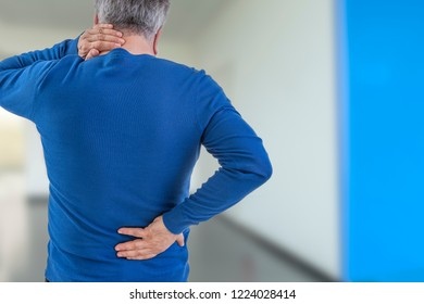 Rear view image of a old man with neck and back injury.