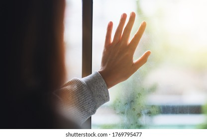 Rear view image of a sad woman touching on window while looking outside