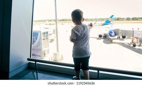 Rear view image of toddler boy touching big glass in international airport terminal