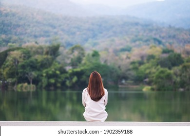 Rear view image of a woman sitting alone by the lake looking at the mountains with green nature background