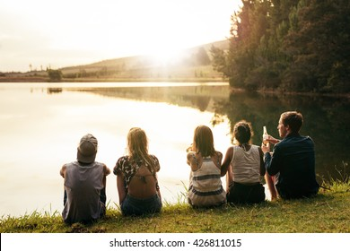 Rear view image of young people sitting in a row by a lake and looking at sunset. Group of friends sitting by a lake and relaxing.