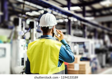 A rear view of an industrial man engineer with smartphone in a factory, working.