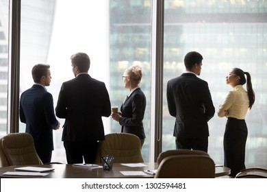 Rear view of international executives team talking near office window, multi ethnic diverse business people silhouette stand back discuss plans, corporate group racial discrimination at work concept