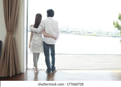 Rear View of a Japanese couple that look out at the window