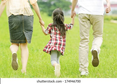 Rear View of Japanese girl walking hand in hand with parents