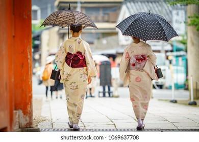 Rear view of japanese women in kimono walking with umbrella