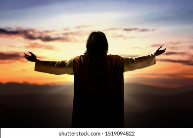 Rear view of Jesus Christ raised hands and praying to god with a sunset sky background
